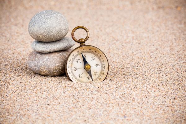 Gesundheitskompass Kompass Kieselsteine im Sand